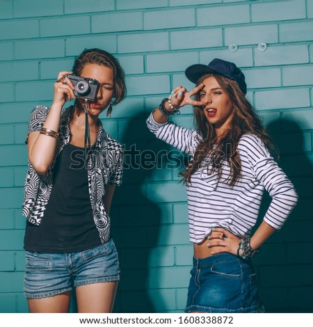Lifestyle portrait of two beautiful best friends hipster girls wearing stylish bright outfits and denim shorts going crazy and having great time. One takes pictures with her camera while her friend.