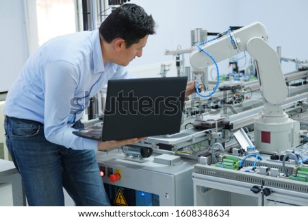 Industry 4.0 concept; Engineer is working on laptop to program robot arm and smart factory automation while automated car on production line is waiting. selective focus. #1608348634