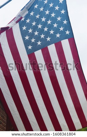 American flag hanging on a flagpole on a house #1608361804
