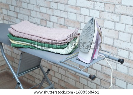 Ironing Board with iron and ironed towels. #1608368461