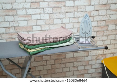 Ironing Board with iron and ironed towels. #1608368464