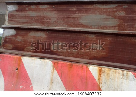 Close up view of a red and white concrete barrier joined with a rusty beam. Signal on a road to delimit works. Abstract image concerning traffic and transportation.  #1608407332