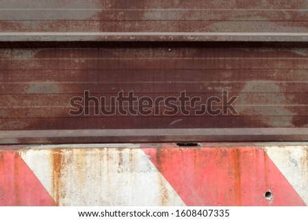 Close up view of a red and white concrete barrier joined with a rusty beam. Signal on a road to delimit works. Abstract image concerning traffic and transportation.  #1608407335