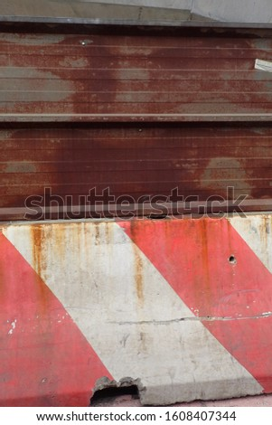 Close up view of a red and white concrete barrier joined with a rusty beam. Signal on a road to delimit works. Abstract image concerning traffic and transportation.  #1608407344