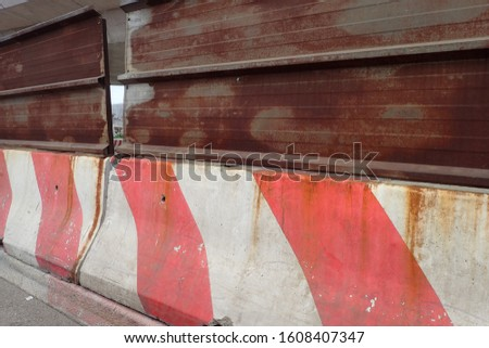 Close up view of a red and white concrete barrier joined with a rusty beam. Signal on a road to delimit works. Abstract image concerning traffic and transportation.  #1608407347