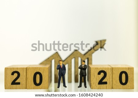 2020 Planning,  Business and Goal Concept. Close up of two businessman miniature figure people standing between wooden number blocks with wood chart arrow icon diecut with copy space. #1608424240