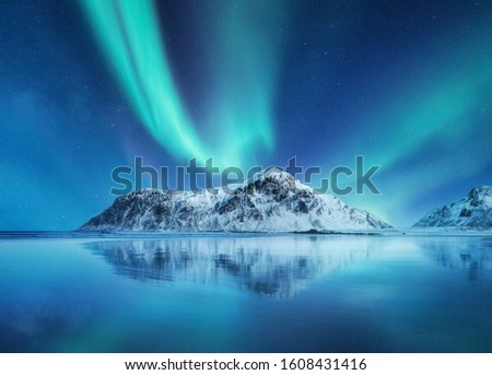 Aurora Borealis, Lofoten islands, Norway. Northen lights, mountains and reflection on the water. Winter landscape during polar lights. Norway travel - image #1608431416