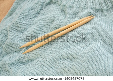 two bamboo knitting needles to lie on a knitted fabric. knitted fabric made of aqua menthol yarn #1608457078