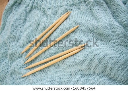 five bamboo knitting needles to lie on a knitted fabric. knitted fabric made of aqua menthol yarn #1608457564