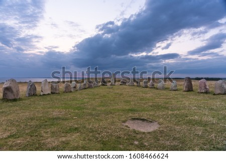 Ales stones on Osterlen in Sweden, a mystical rock formation from the early iron age. A night view with twilight from the pink colored setting sun and a dark overcast sky #1608466624