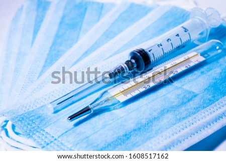 Syringe for injection and a thermometer on the background of medical masks. #1608517162