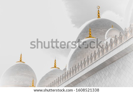 Abu Dhabi grand mosque in white with the golden howl moon on the dome and a white background, creative abstract photography  Royalty-Free Stock Photo #1608521338