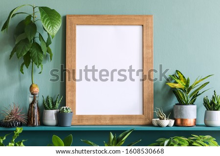 Interior design of living room with brown mock up photo frame on the green shelf with beautiful plants in different hipster and design pots. Elegant personal accessories. Home gardening. Template.  Royalty-Free Stock Photo #1608530668