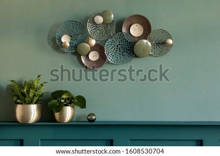 Stylish and modern composition of living room. Green wall panelling with shelf.  Beautiful plants in gold pots, decoration and elegant personal accessories. Modern home decor. Template. Copy space. Royalty-Free Stock Photo #1608530704