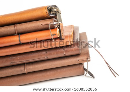 A stack of leather-bound journals, notebooks, cases and wallets set on a plain white background. #1608552856