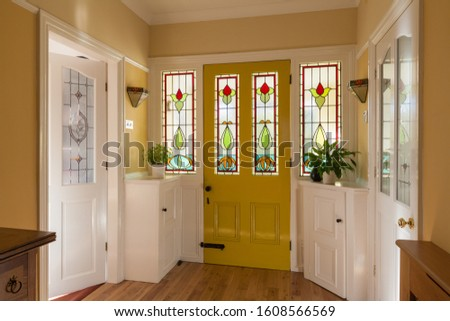 Front door and hallway of a house in England with stained glass window in the door. Royalty-Free Stock Photo #1608566569