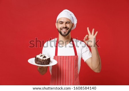 Bearded male chef cook or baker man in striped apron white t-shirt toque chefs hat posing isolated on red background. Cooking food concept. Mock up copy space. Hold plate with cake showing OK gesture #1608584140