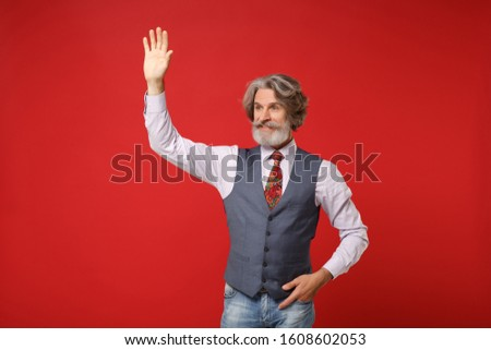 Elderly gray-haired mustache bearded man in classic shirt vest colorful tie isolated on red background. People lifestyle concept. Mock up copy space. Waving and greeting with hand as notices someone #1608602053