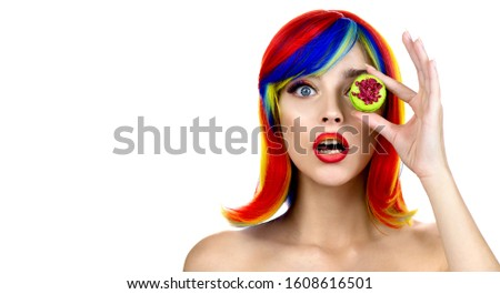 Beautiful fashion model with colored rainbow eyelashes, multi-color wig and creative color makeup holds macaroon sweetie and shows surprised facial expression.  #1608616501