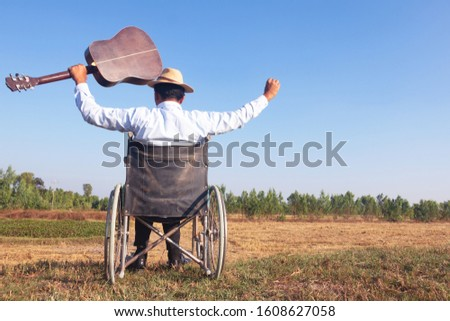 Young disabled man and field background. He is raising guitar and looking into sky.He is wearing a hat and sitting on wheelchair.despair,lonely,hope.Photo concept depression and Patient. #1608627058