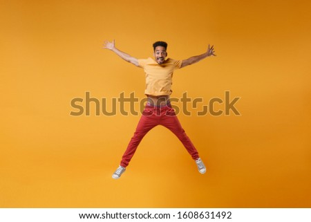 Funny young african american guy in bright casual clothes posing isolated on yellow orange background studio portrait. People lifestyle concept. Mock up copy space. Jumping spreading hands and legs #1608631492