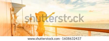 Cruise ship vacation travel woman having fun feeling free enjoying luxury elegant lady carefree on deck watching sunset on Caribbean winter holidays banner panorama. Cruiseship sailing on holiday.