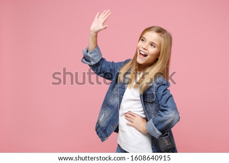 Cheerful little blonde kid girl 12-13 years old in denim jacket isolated on pastel pink background. Childhood lifestyle concept. Mock up copy space. Waving and greeting with hand as notices someone #1608640915