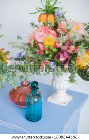 Workshop on creating a bouquet and floral arrangements in the style of boho chic. Pink peonies, red roses, green eucalyptus. Bouquets in ceramic vases on a wooden blue table. #1608644686