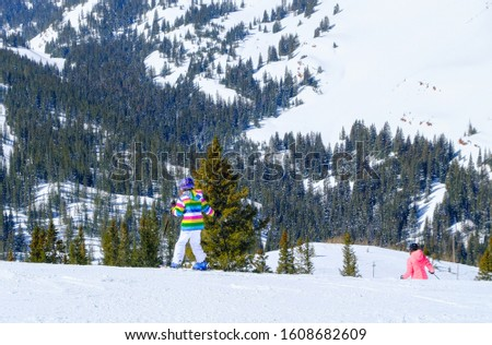 Young female skier on Colorado ski slope near Aspen, Colorado, USA; snow covered slopes and trees in background #1608682609