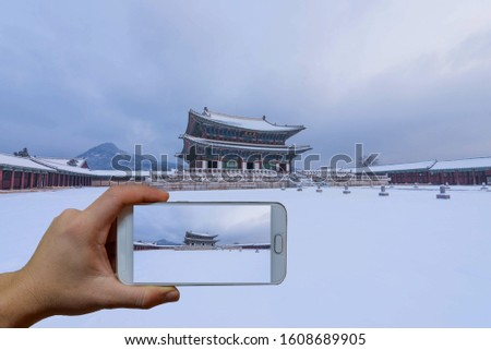 Hand taking picture of Gyeongbokgung Palace with cell phone at Gyeongbokgung Palace in winter snow in Seoul,South Korea.