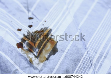 Dirty sauce stain on blue skirt from accident in eating. daily life dirt stains for cleaning and washing concept  #1608744343