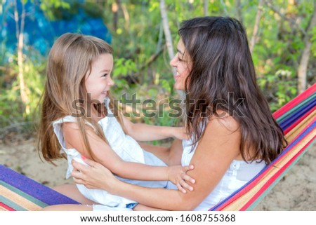 A young mother with her little daughter is resting in a hammock on the beach on a summer sunny day. #1608755368