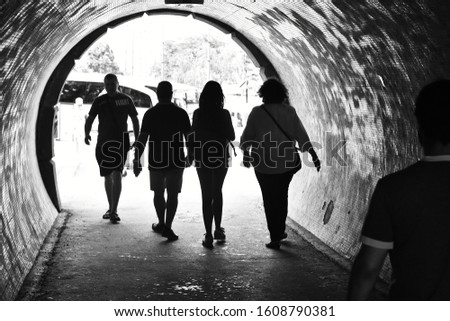 Budapest, Hungary - July 9, 2018: Silhouettes of people passing through a tunnel in Budapest, Hungary  (Black and White, monochrome) #1608790381