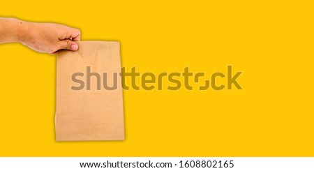 Hand holding paper bag on yellow background, panoramic banner cover background concept with copy space. #1608802165
