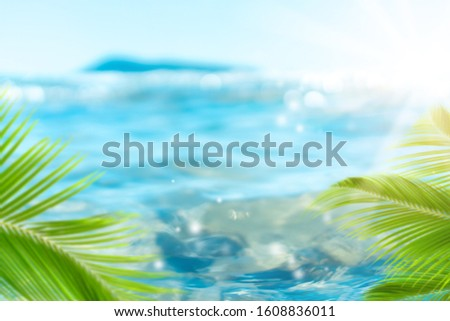 Blur beautiful nature green palm leaf on tropical beach with bokeh sun light wave abstract background. Copy space of summer vacation and business travel concept. Vintage tone filter effect color style #1608836011