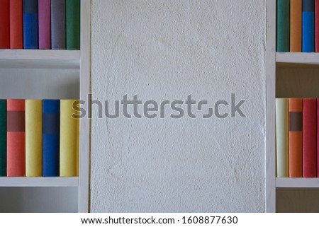 White wall with part of bookshelves with colorful books #1608877630