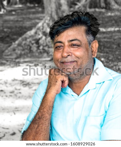 Happy and healthy Middle aged Indian male in his early 50s, posing for photo with cheerful and smiling face, with hand on chin. He is retired and living a satisfied life. B&W background for editing.