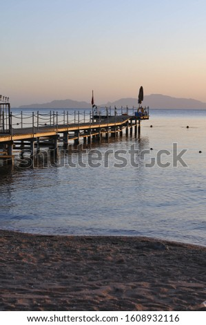 Pier at sunrise. Beautiful picture. Wooden pier on the background of the sea and islands. #1608932116