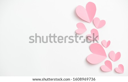 Paper elements in shape of heart flying on white paper background. Love and Valentine's day concept. Birthday greeting card design.