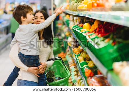 woman and child boy during family shopping with trolley at supermarket #1608980056