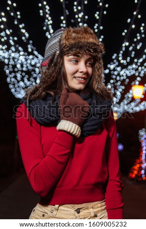 Girl in a winter hat on a background of festive illumination. New Year and Christmas mood. Female portrait #1609005232
