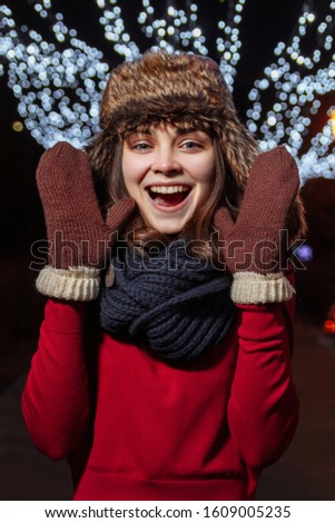 Girl in a winter hat on a background of festive illumination. New Year and Christmas mood. Female portrait #1609005235