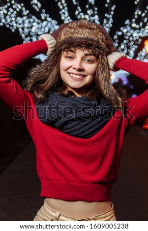 Girl in a winter hat on a background of festive illumination. New Year and Christmas mood. Female portrait #1609005238