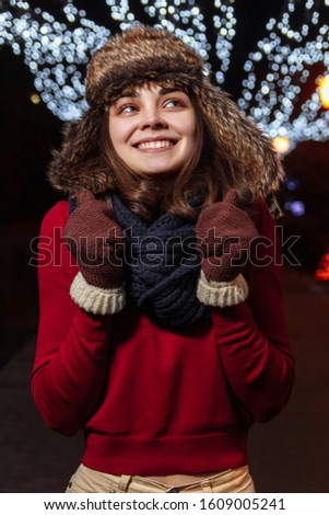 Girl in a winter hat on a background of festive illumination. New Year and Christmas mood. Female portrait #1609005241