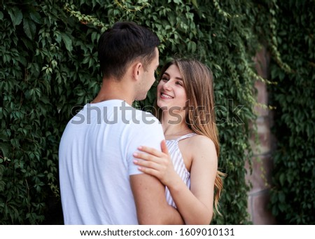 Young couple in love hugging near green bushes trees wall. Pretty blond woman, wearing stripy short overall and brunette man in white t-shirt and blue shorts on romantic date. Romantic relationship #1609010131