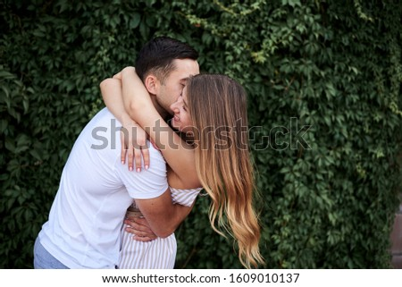 Young couple in love hugging near green bushes trees wall. Pretty blond woman, wearing stripy short overall and brunette man in white t-shirt and blue shorts on romantic date. Romantic relationship #1609010137