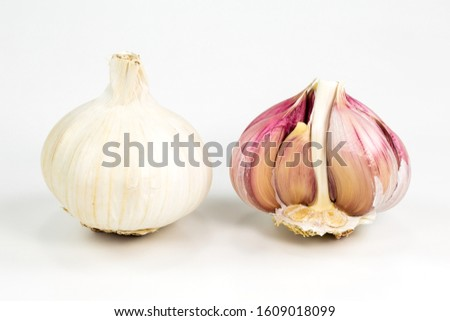 a close white organic garlic bulb with skin and a semi-peeled garlic bulb isolated on white background #1609018099