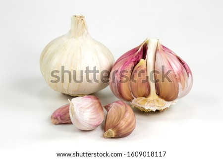 one closed white organic garlic bulb with skin and one opened semi-peeled garlic bulb and cloves isolated on white background #1609018117