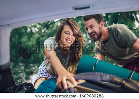 Young couple having fun while unpacking camping equipment #1609080286