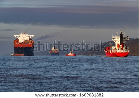 Vessels with Containers and other freight leaving Hamburg Harbour down the River Elbe to the North sea as symbol of global Trade and international water traffic #1609081882